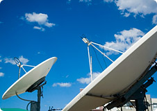 Satellite Dishes under a blue sky with small clouds in the background
