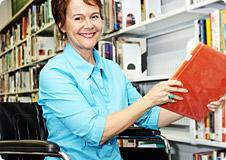 stock photo woman putting books on library shelf