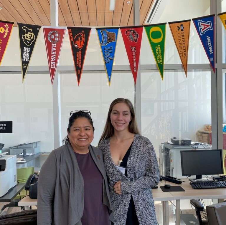 SCDC Director Emma Hernandez poses for a photo with a intern below a colorful college banners.
