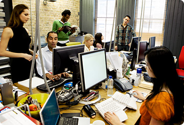 Open workspace with people collaborting on computers
