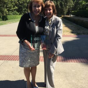 Photo: State Secretary Karen Ross and Sunne Wright McPeak stand together holding the 2018 CA State Fair Award for Individual Championstands next to her.