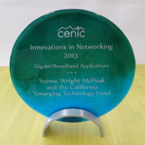 Photo of a circular glass award. The award is for the 2013 CENIC Innocations in Networking Gigabit/Broadband Applications - Sunne Wright McPeak and CETF