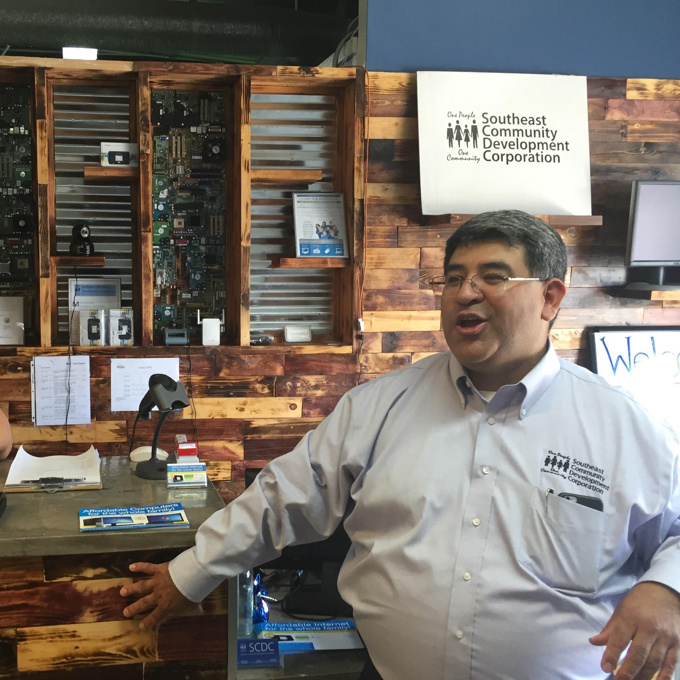 SCDC Director, Cesar Zaldivar-Motts stands at the wooden bar of SCDC's Internet Cafe